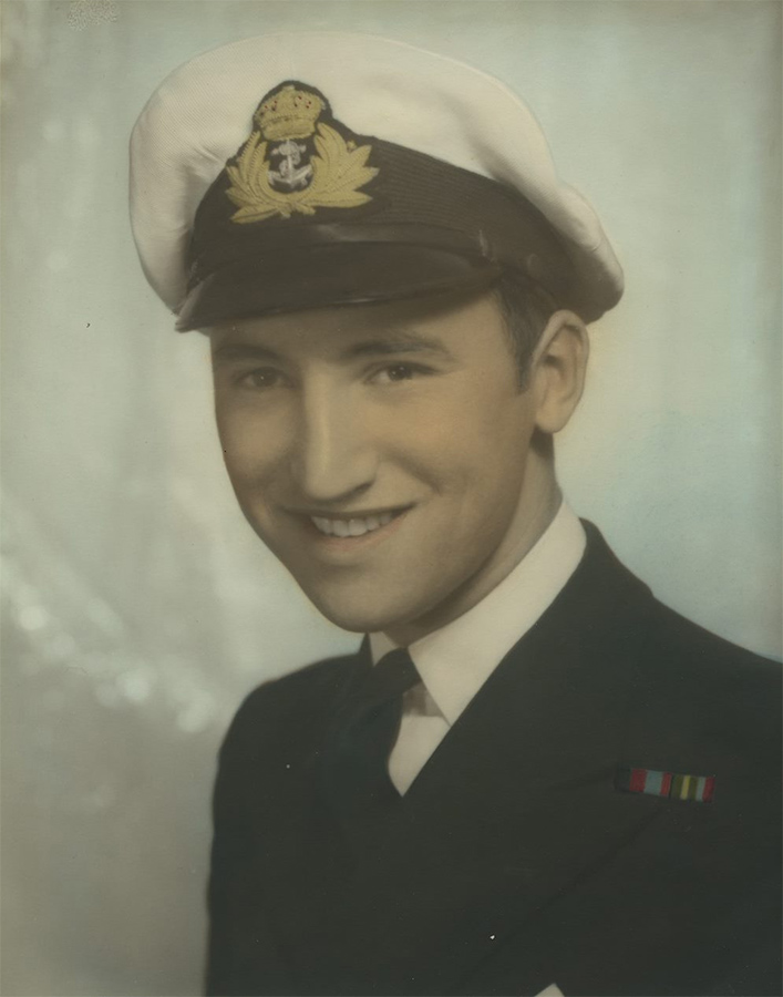 A hand coloured headshot of a young man in a naval uniform. The man is looking towards the camera and smiling.