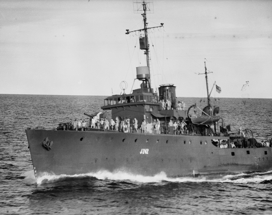 A black and white photograph of a military ship cutting through the ocean. Groups of men can be seen standing on the deck of the ship.